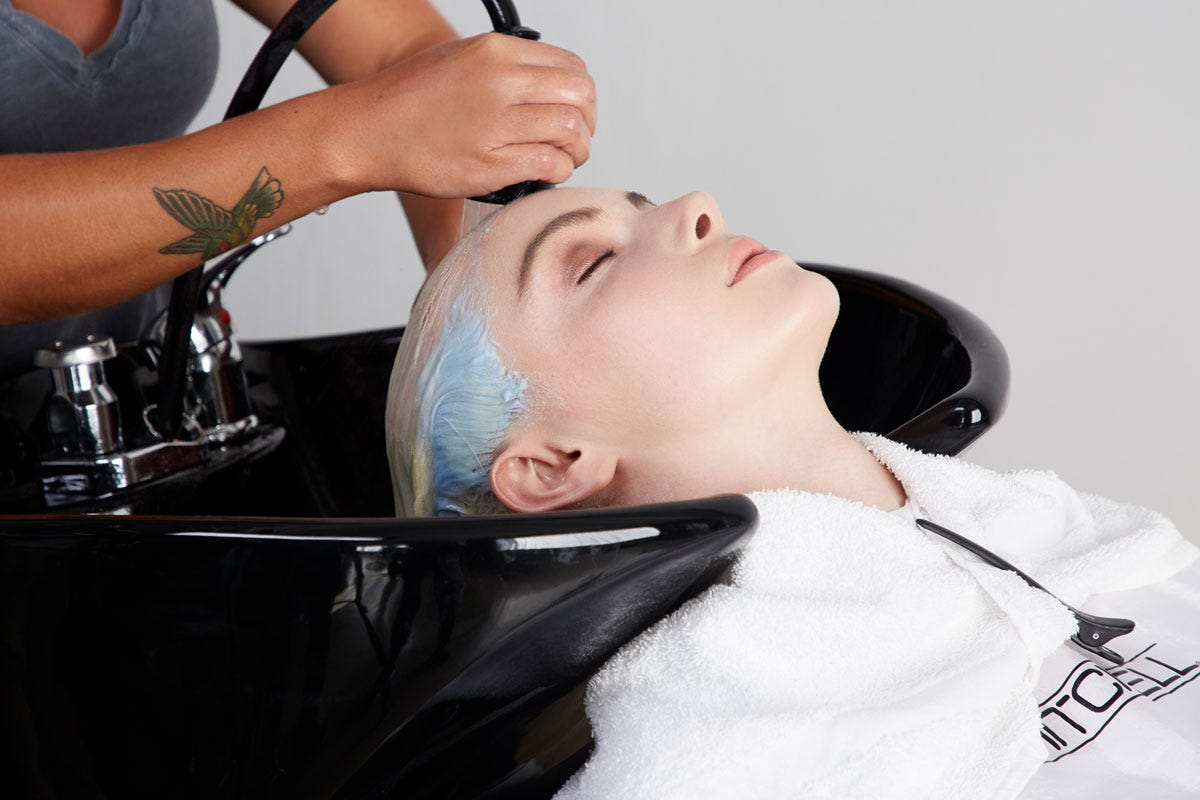 A model in the process of getting her hair colored. In this image the hair color is being washed out of models hair.