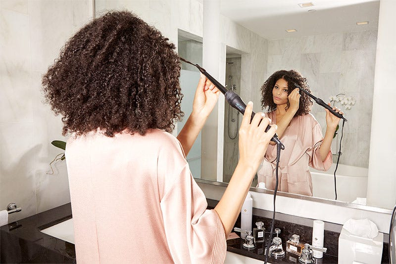 MarulaOil How-To: Gorgeous Curls Step 8 of 10. Woman using Neuro Unclipped Small Styling Cone.