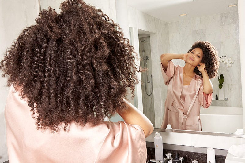 MarulaOil How-To: Gorgeous Curls Step 9 of 10. Woman running her fingers through to add volume.