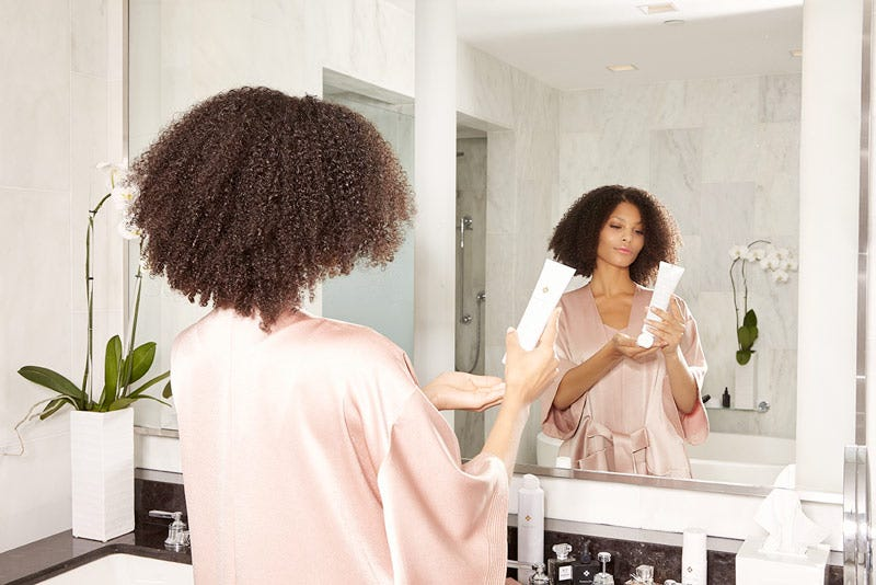 MarulaOil How-To: Gorgeous Curls Step 1 of 10. Woman standing in front of mirror holding a  bottle of Rare Oil 3-in-1 Styling Cream.