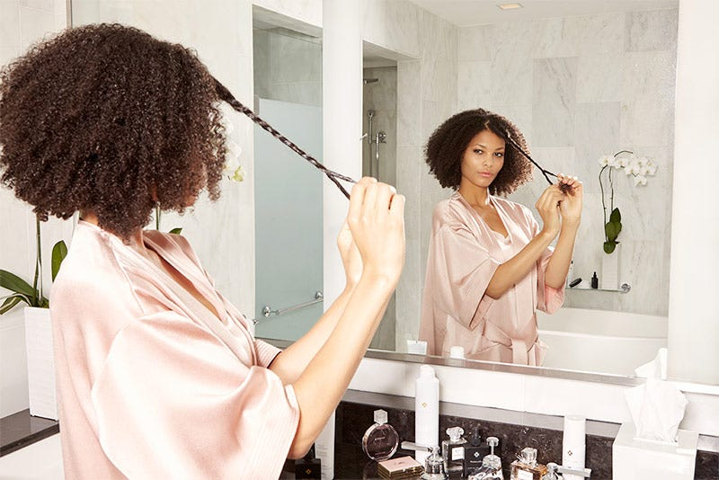 MarulaOil How-To: Gorgeous Curls Step 4 of 10. Woman twisting hair sections.
