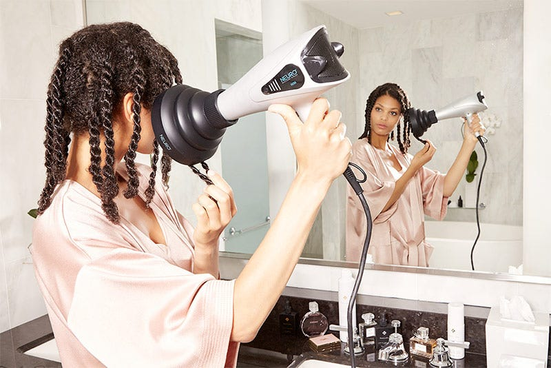 MarulaOil How-To: Gorgeous Curls Step 6 of 10. Woman using Neuro Light hair dryer on twists of hair.