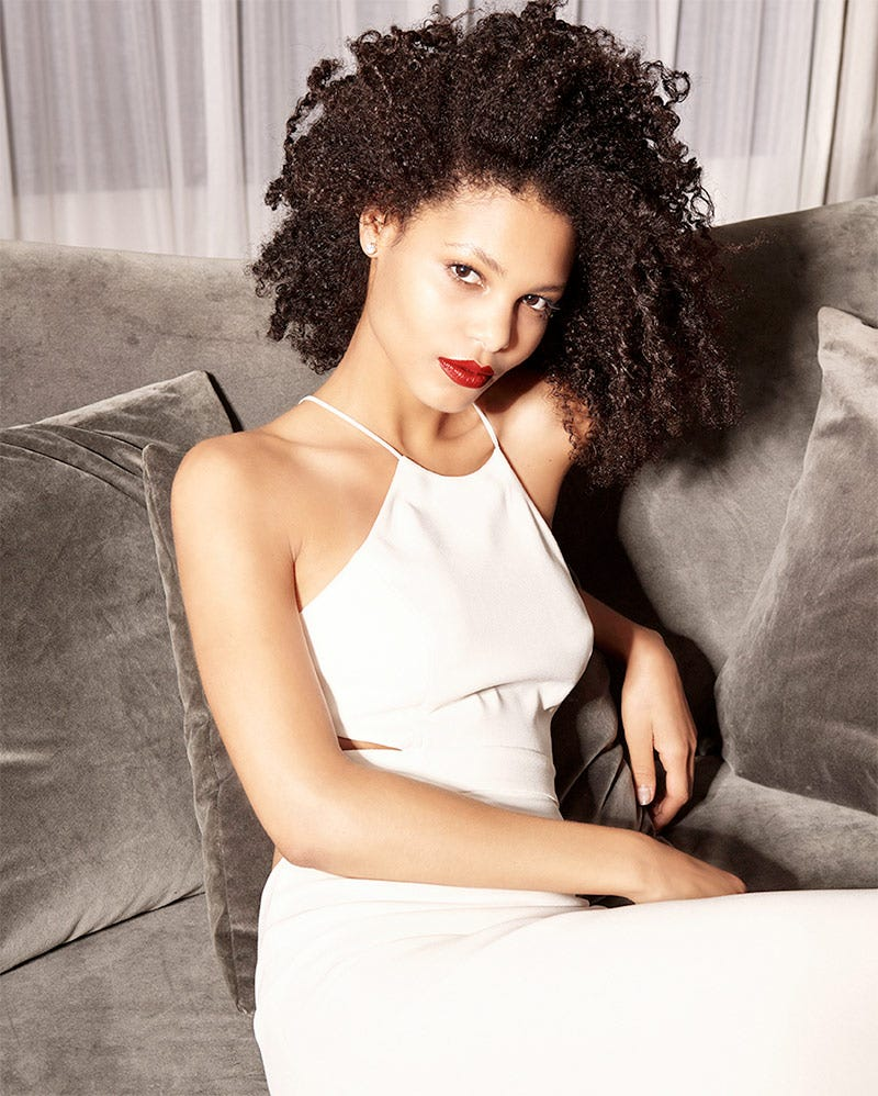 MarulaOil How-To: Gorgeous Curls Finished Look. Woman with beautiful curly hair in white dress sitting on a brown couch.
