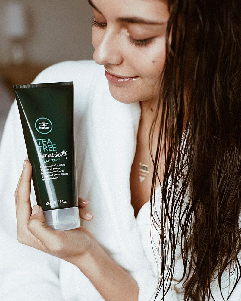 image of tea tree model holding tea tree hair and scalp treatment